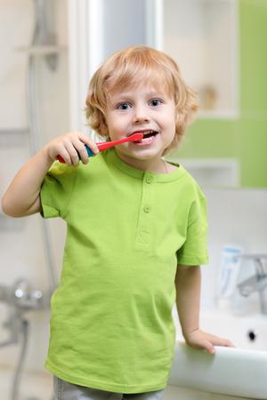 Cute little child boy brushing teeth in bathroom