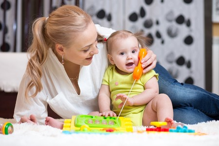 Cute mother and kid playing toy phone indoor