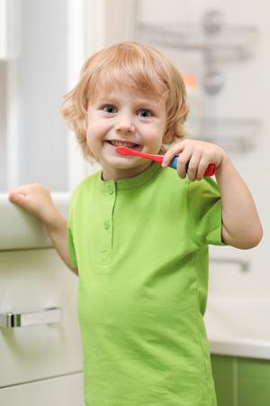 Little child boy brushing teeth in bath