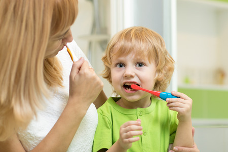 Mother and child boy brushing teeth together Stock Photo