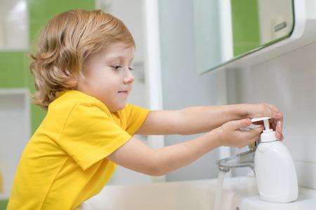 Cute kid boy washing his hands