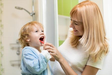 Mother teaching son child teeth brushing in bathroom Stock Photo