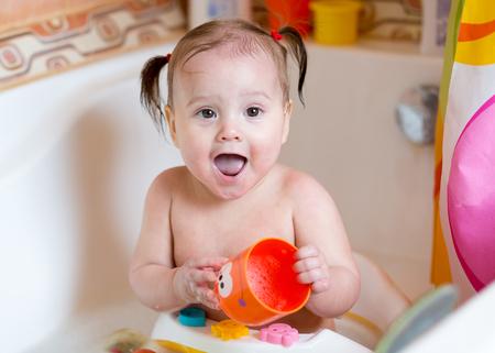 Cute baby girl washing in bathroom
