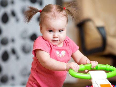 Portrait of pretty toddler girl standing with baby walker