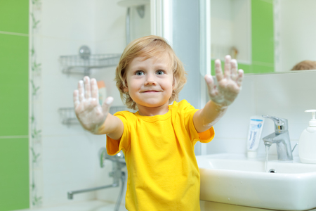 Smiling child boy washing hands and showing soapy palms