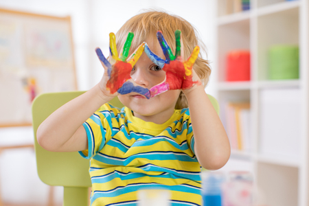Cute cheerful kid with hands painted in bright colors at art class Stock Photo