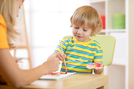 Child boy with teacher drawing paints in play room. Preschool. Stock Photo