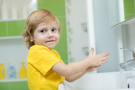 little child boy in a bathroom washing hand with soap Stock Photo