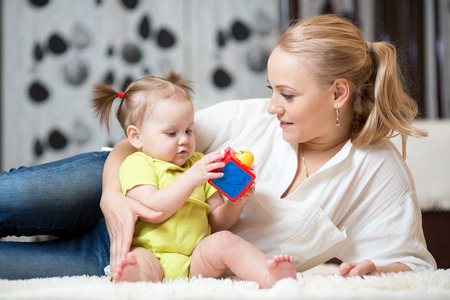 Cute woman playing with her baby daughter in while sitting on a carpet in the living room Stock Photo