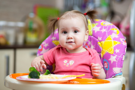 baby girl eating broccoli and sitting in highchair