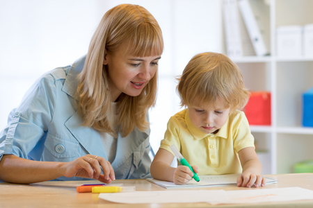 Cute child boy drawing and writing with colorful markers pens at kindergarten. Creative kid painting at playschool. Teacher or mother helps to little pupil. Stock Photo