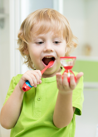 Little toddler child boy brushing his teeth and looking at hourglass