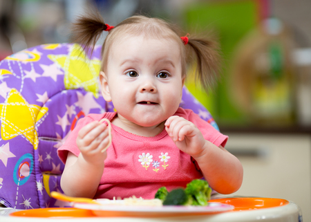 Baby girl eats pasta with vegetables sitting in highchair in kitchen