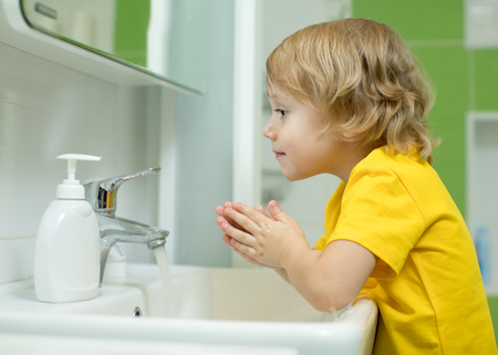 Child boy washing his face in the bathroom