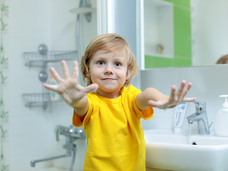 Toddler boy washing hands and showing soapy palms
