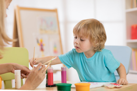 little cute boy painting pictures in art studio Stock Photo