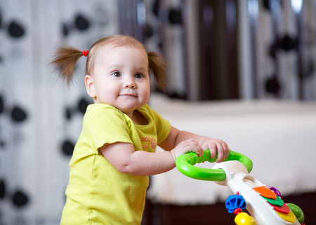 First steps of little kid girl in baby walker Stock Photo