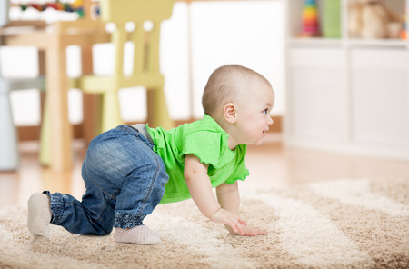 side view of baby crawling on carpet on floor in children room