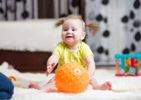 babyhood and people concept - happy baby playing with ball on floor at home Stock Photo