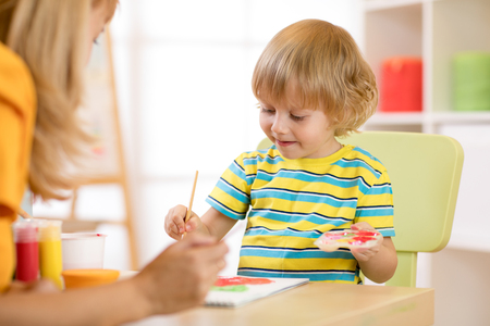 Little boy painting with teacher in classroom