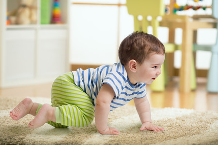 Baby playing and crawling on a rug on the floor Stock Photo