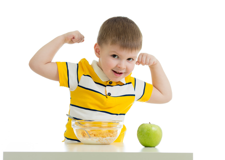 child boy eating healthy food and showing his strength, isolated on white