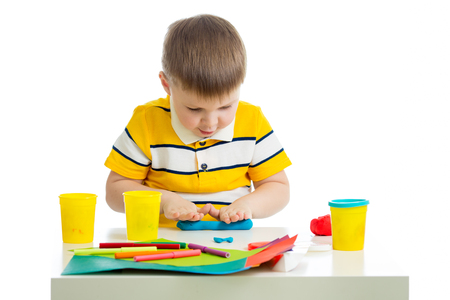Little kid boy sitting at table and sculpting from plasticine. Isolated on white background. Stock Photo