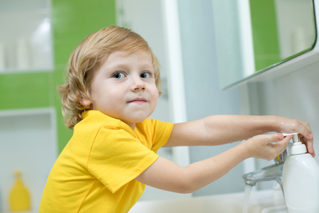 Little boy washing his hands in the bathroom Stock Photo