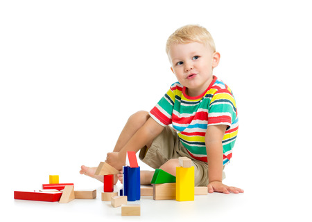 Little child boy playing cubes sitting . Isolated on a white background.