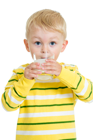 Child boy drinking dairy product from glass isolated on white