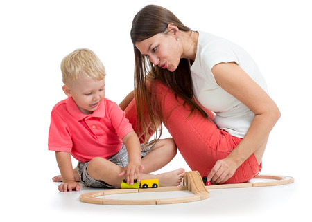 child boy and his mother play with railroad toy