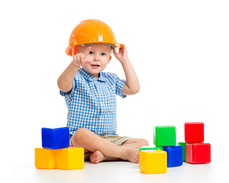 smiling child boy with hard hat playing cubes, isolated on white