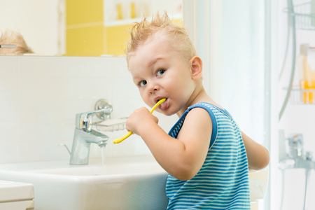 Smiling child kid toddler boy brushing and clean teeth in bathroom himself.