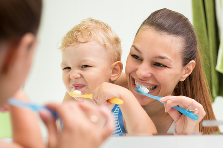 Beautiful mother helping her child son to brush teeth in bathroom Stock Photo