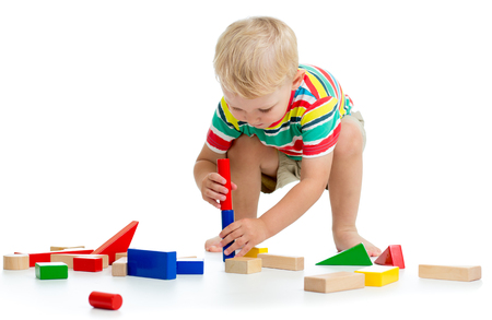 Little kid boy playing with toys isolated on white background Stock Photo