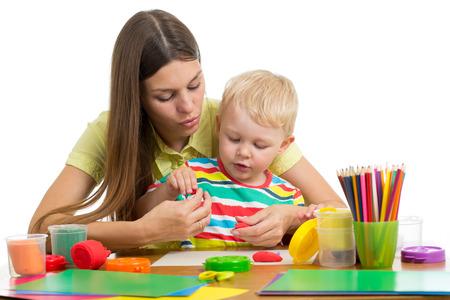 woman teaches kid boy handcraft at kindergarten or playschool