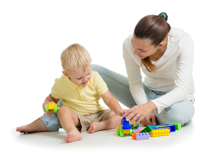 Family playing together. Mom and son play building block toys. Mother and child sitting on the floor. Isolated on white Stock Photo