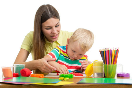 Cute woman and kid boy playing plasticine toys at home, isolated