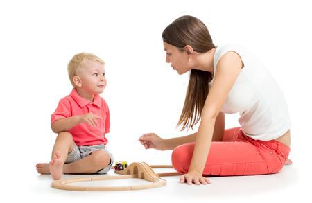 Cute woman and kid girl playing railway toys at home, isolated Stock Photo