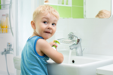 child toddler boy washing his face and hands with soap in bathroom Stock Photo