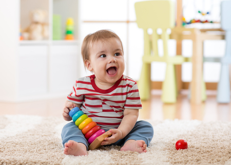 Baby toddler boy playing indoors with developmental toy sitting on soft carpet Stock Photo