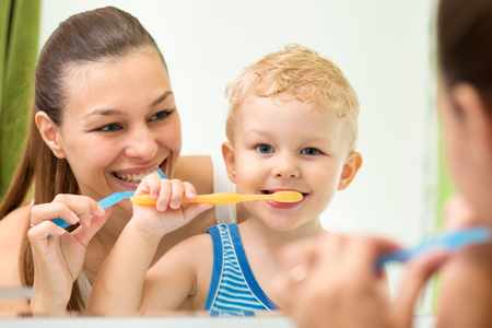 Pretty woman and her son brushing their teeth and looking at miroor in bathroom