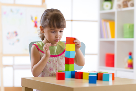 Little child girl playing with wooden colorful cubes Stock Photo