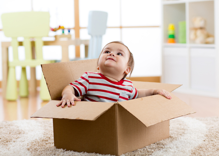 cute little baby boy sitting inside cardboard box, moving out concept
