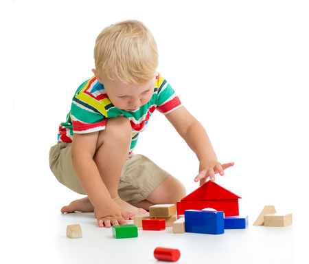 Child boy building castle with colorful wooden cubes