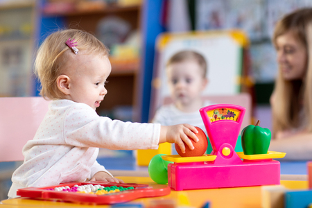 Kids with preschool teacher play role game in toy shop at home or kindergarten Stock Photo