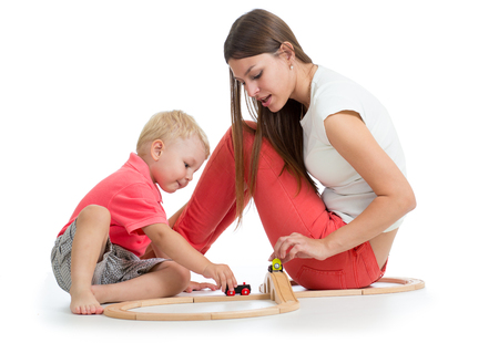 Child boy playing with railway toys on floor, isolated on white. Mother helps to her son. Stock Photo