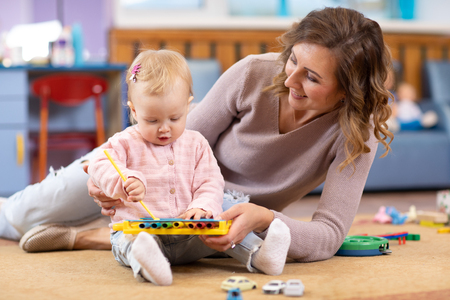 Young mother and cute baby playing on floor at home or playroom. Mom teaching her little girl how to play on toy metallophone Stock Photo