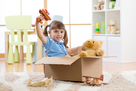 Happy child little girl plays pilot sitting into cardboard box in flat Stock Photo
