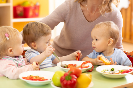 Babies eating healthy lunch in nursery or daycare centre